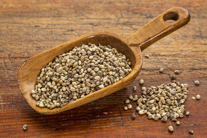 Семена конопли на деревянном совке , на деревянной поверхности