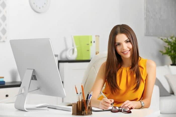 Девушка в желтой кофте с ручкой в руках сидит перед компьютером