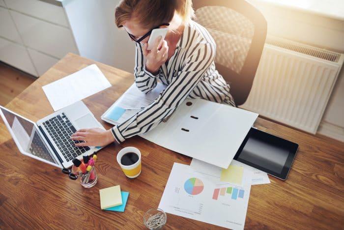 Девушка в полосатой рубашке говорит по телефону и печатает на ноутбуке