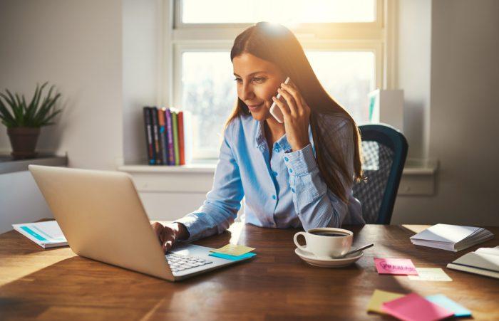девушка говорит по телефону сидя перед ноутбуком с чашкой кофе