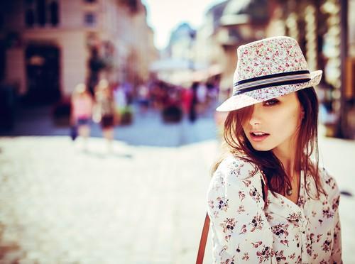 Девушка в блузке с цветочным принтом и в шляпе