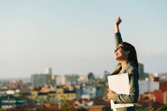 Девушка в очках с папкой на крыше подняла руку