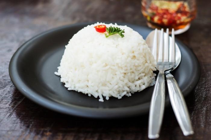 приготовленный рис с ложкой и вилкой на тарелке