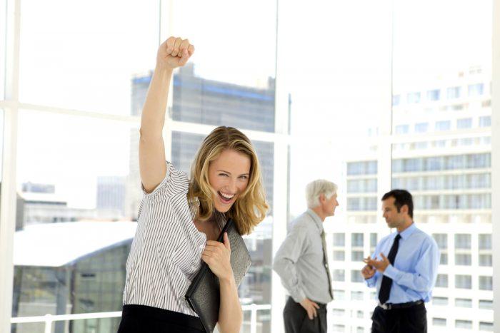 Счастливая женщина с папкой в руках радуется на фоне мужчин
