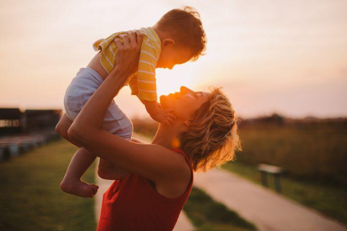 Женщина на закате подняла над собой ребенка