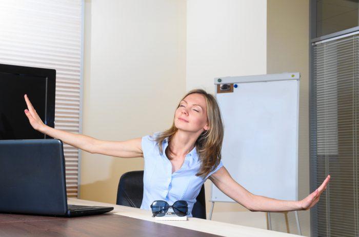 Женщина сидя в офисе расстправила руки и мечтает