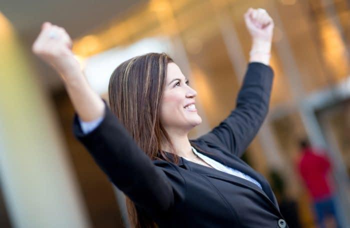 Женщина в черном пиджаке подняла руки вверх