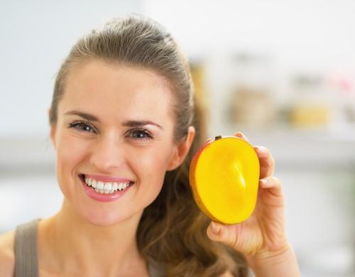 Девушка кушает манго