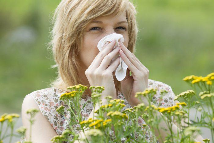 Девушка закрыла нос из-за аллергии на цветы