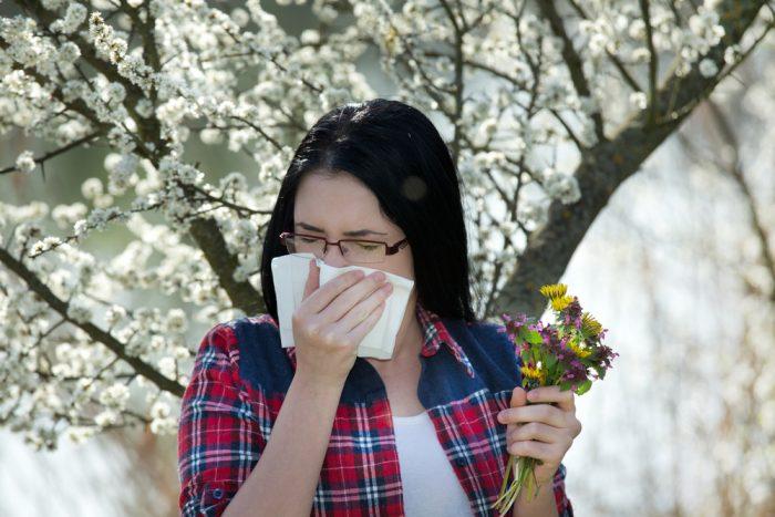 Девушка прикрыла нос из-за аллергии на цветы