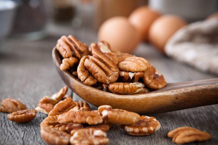 Орех пикан на деревянной ложке