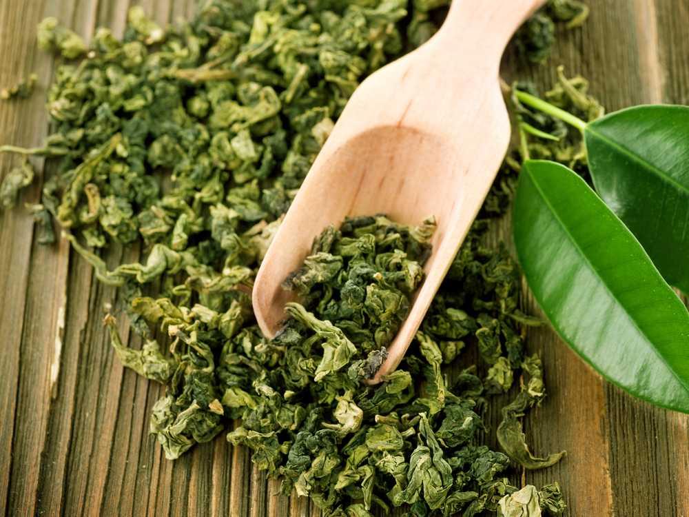 Сухой зеленый чай с деревянной лопаткой