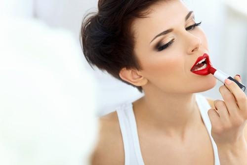 Девушка в белой майке красит губы красной помадой