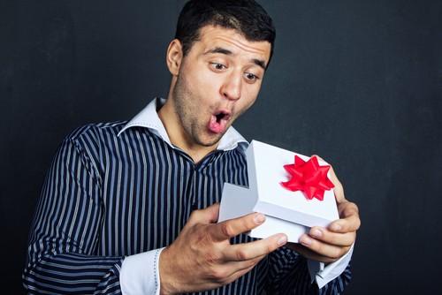мужчина открывает подарок
