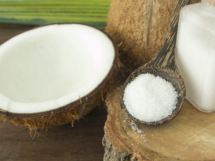 Деревянная ложка с солью возле половины кокоса