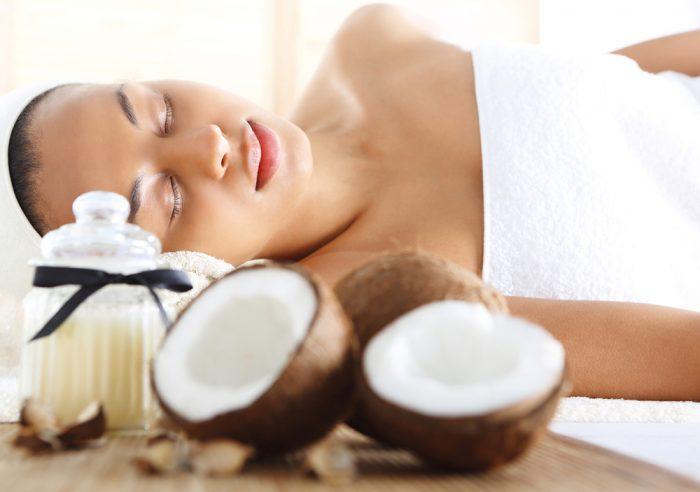 Девушка в белом полотенце лежит возле кокоса