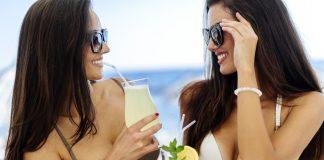 Две девушки в очках, в купальниках с коктейлями