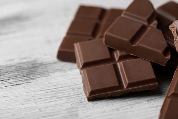 Кусочки плитки черного шоколада на деревянной поверхности