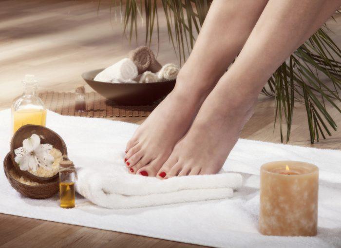 Женские ножки на белом полотенце в спа