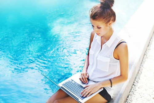 девушка с ноутбуком возле бассейна