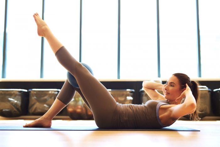 Девушка делает упражнение поднимая ногу