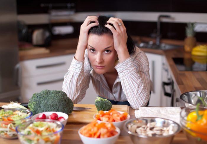 Девушка расстроенная над едой в тарелках
