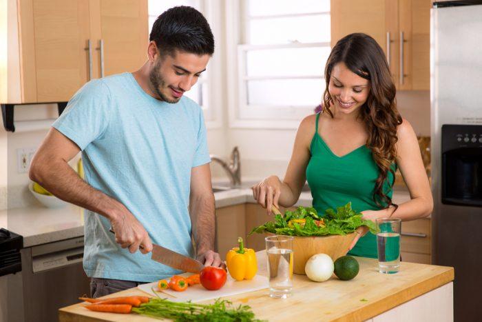 Парень режет овощи и девушка готовит салат