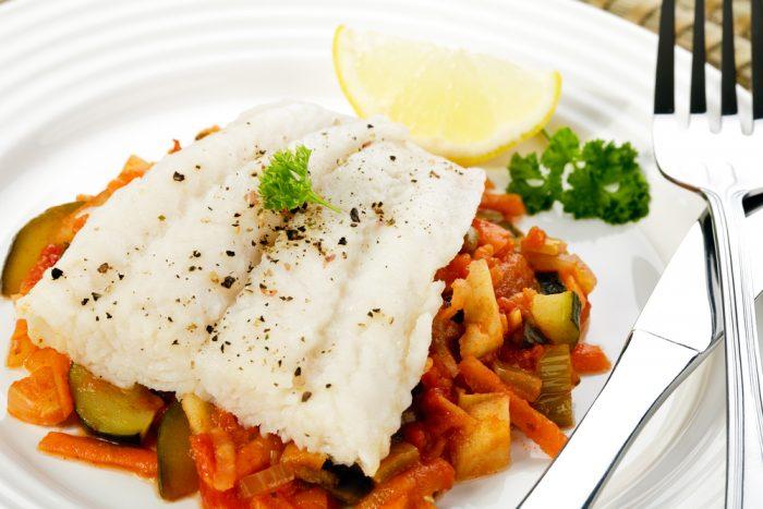 тарелка с белой рыбой на овощах с долькой лимона