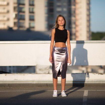 Девушка в черном топике и серебряной юбке ниже колен