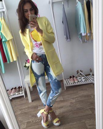 Девушка в джинсах, в пиджаке из неопрена нежно жёлтого цвета ив босоножках
