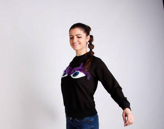 Девушка с черном свитере с глазками