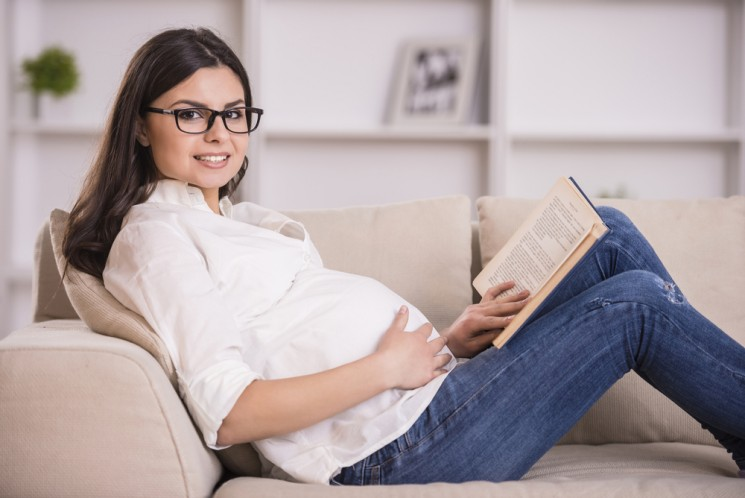 Беременная девушка в очках читает книгу, лежа на диване