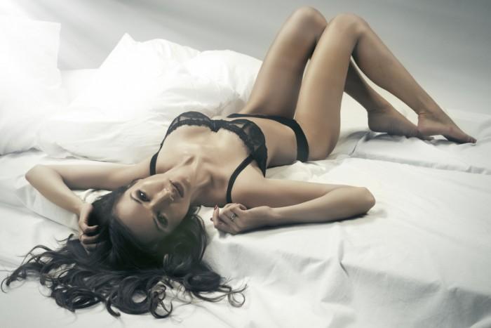 Девушка лежит на белой кровате в черном нижнем белье на стене и смотрит в фотокамеру