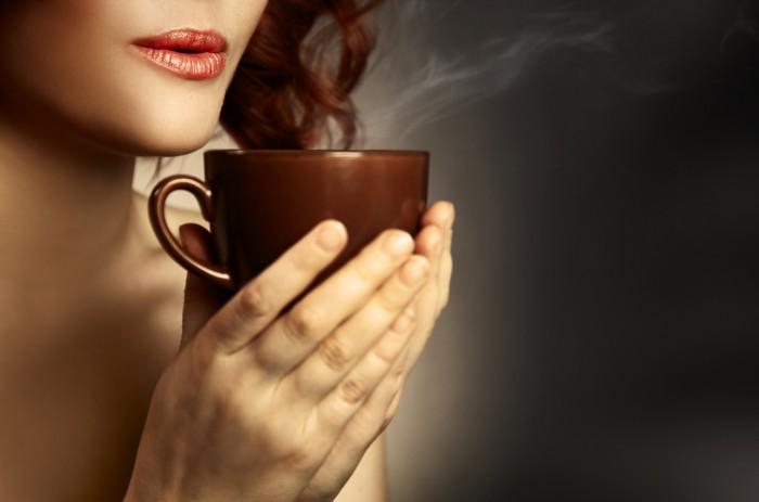 Девушка держит чашку ароматного кофе в руках