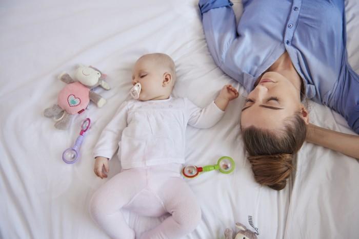 Девушка возле ребенка уснула