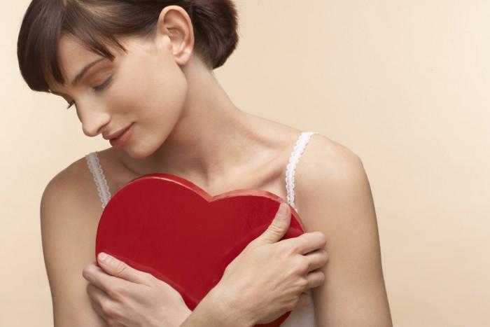 Девушка обнимает красное пластмассовое сердце