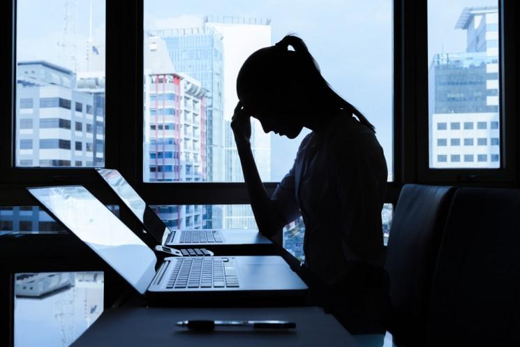Уставшая девушка сидит в офисе за ноутбуком