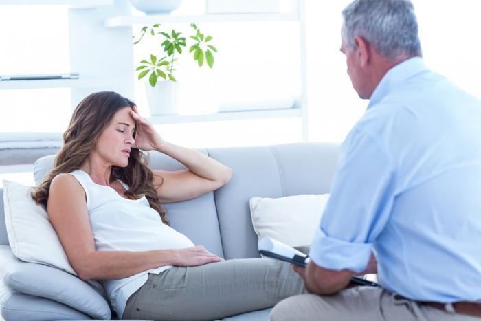 Беременная девушка говорит с доктором