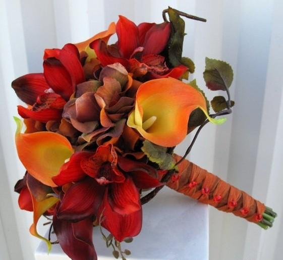 букет невесты из нежных орхидей, красных, оранжевых и коричневых калл