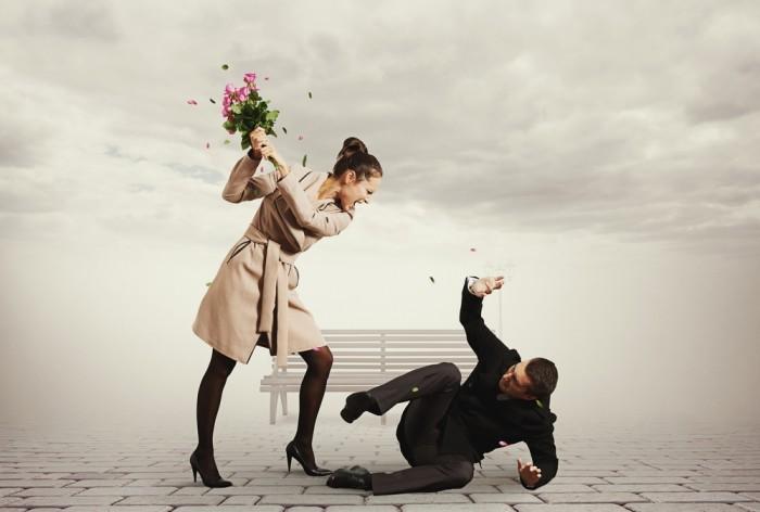 Девушка бьет парня букетом цветом возле лавочки