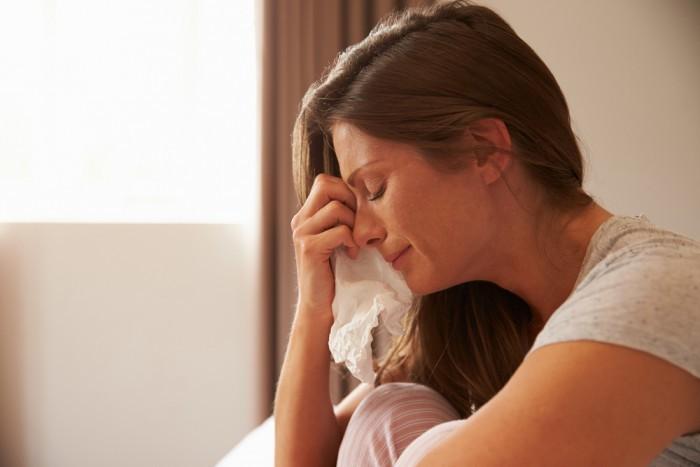 Девушка плачет прикрывая лицо платком