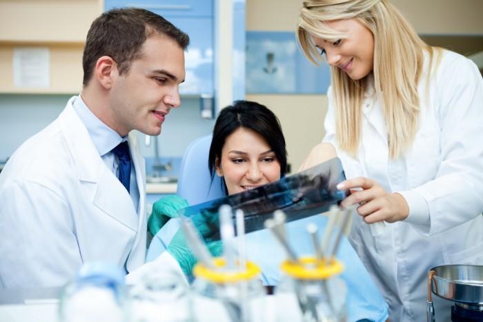 Стоматолог показывает пациенту снимок рентгена зубов