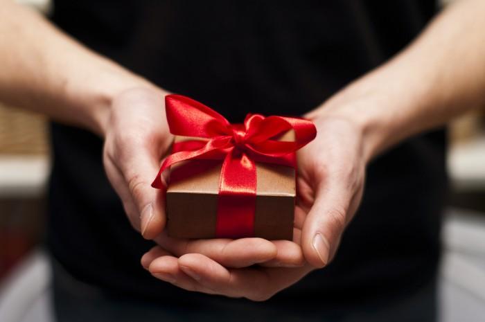 Подарок в коричневой коробочке перевязанной красной ленточкой держит в руках женщина