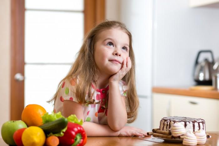 Девочка выбирает между овощами и сладостями