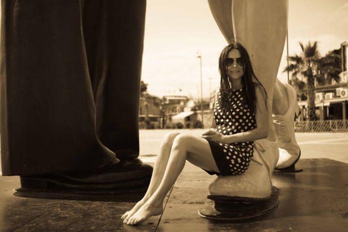 Анастасия Даугуле сидит в коротком платье и босиком