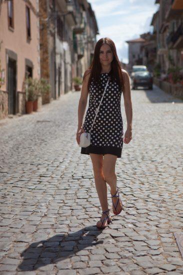 Анастасия Даугуле в платье горошек и белая сумка через плечо