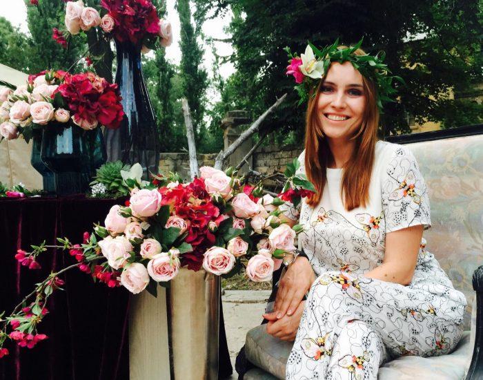 Анастасия Даугуле возле цветом с венком на голове