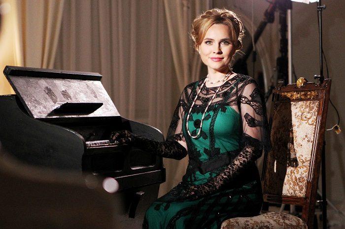 Анастасия Даугуле в зеленом платье с черным кружевом перед роялем
