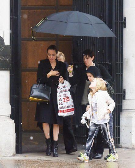 Анджелина Джоли в черном пальто с и с детьми