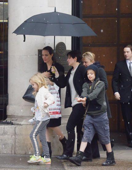 Анджелина Джоли в черном платье с детьми под зонтом